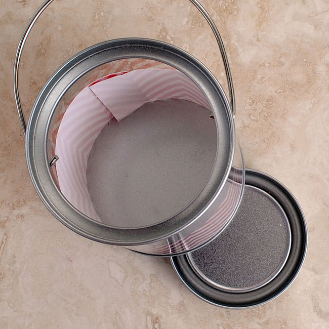 Place the paper gift wrap strip inside the mini paint can and tape the seam.